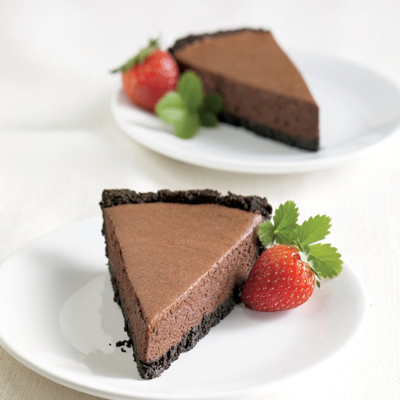 Two slices of chocolate pie with a cookie crust and strawberry garnish.